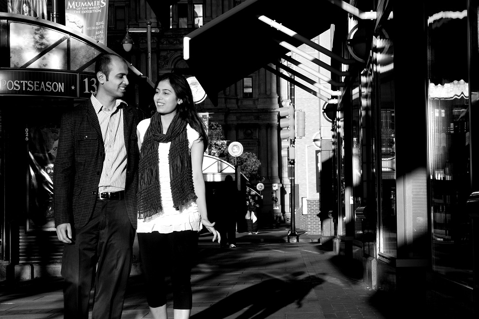 Black and white photograph if couple walking down the street